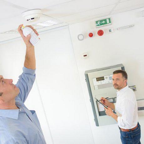 technician checks fire panel in data center